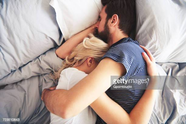 couple lying in bed together, sleeping, arms around each other - romantic young couple sleeping in bed stock photos and pictures