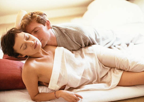 Couple lying in bed, woman wrapped in sheet, man behind her in t-shirt
