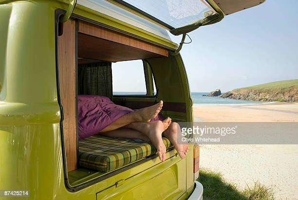 Couple lying in camper van