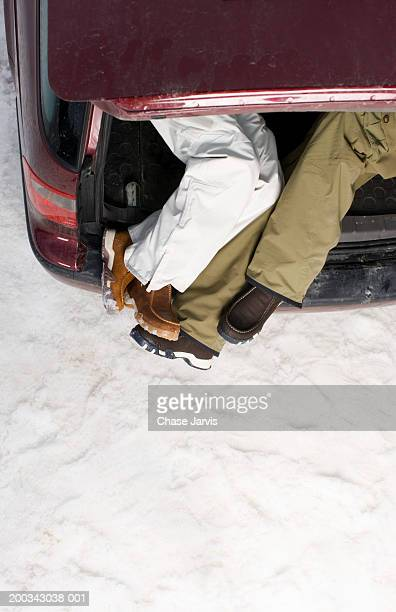 Couple lying in car trunk with feet hanging out back, overhead view