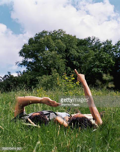 couple lying in grass, looking at sky and clouds - lying down imagens e fotografias de stock