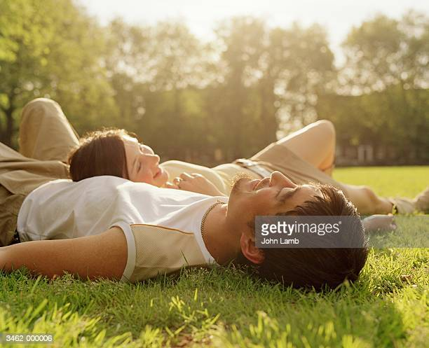 couple lying in park - lying down stock pictures, royalty-free photos & images