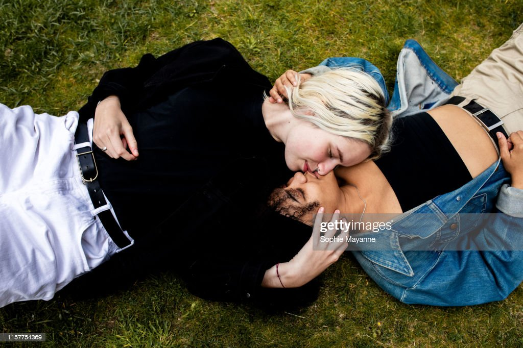 LGBT couple lying in the grass kissing : Stock Photo