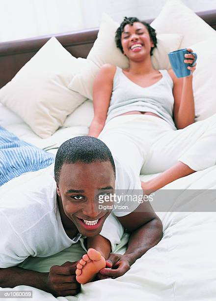 couple lying on a bed, man tickling woman's foot - woman lying on stomach with feet up stock photos and pictures