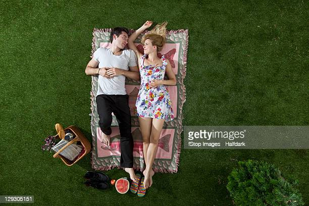 A couple lying on a blanket in a park looking at each other romantically, overhead view