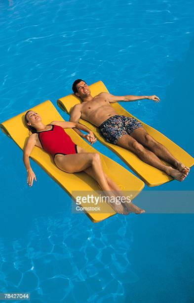 Couple lying on a raft in swimming pool