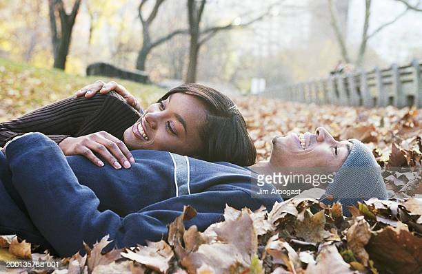 Couple lying on autumn leaves in park, side view