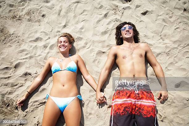 Couple lying on beach, holding hands, smiling, overhead view