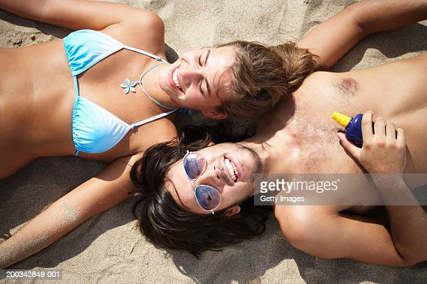 Couple lying on beach, smiling, overhead view