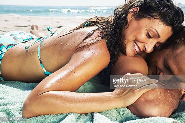 couple lying on beach, woman resting head on man's shoulder, close-up - homem moreno imagens e fotografias de stock