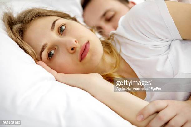 couple lying on bed at home - amanti letto foto e immagini stock