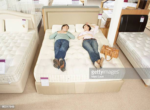 Couple lying on bed in furniture store.