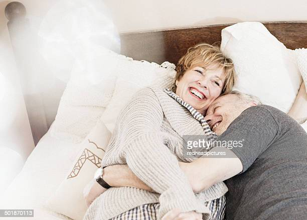 Couple lying on bed laughing