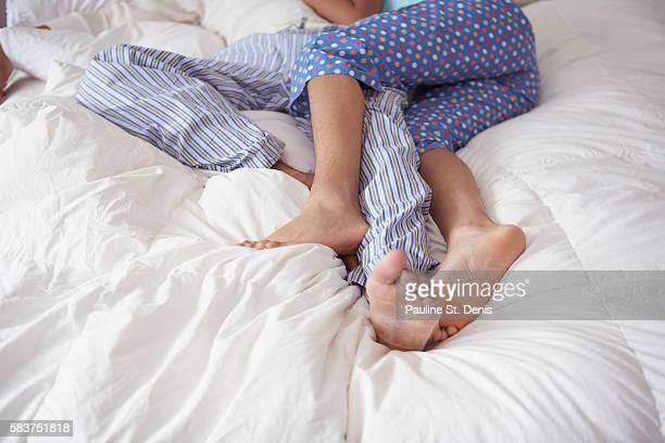 Couple lying on bed, legs intertwined
