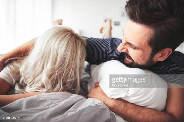 couple lying on bed, man tickling woman - kitzeln stock-fotos und bilder