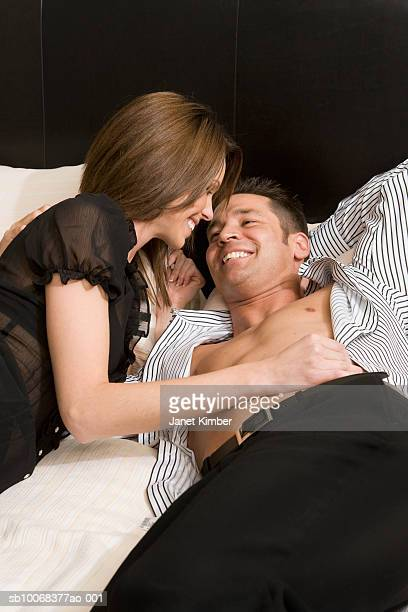 Couple lying on bed, smiling