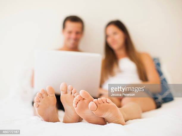 couple lying on bed with laptop - male feet soles stock photos and pictures