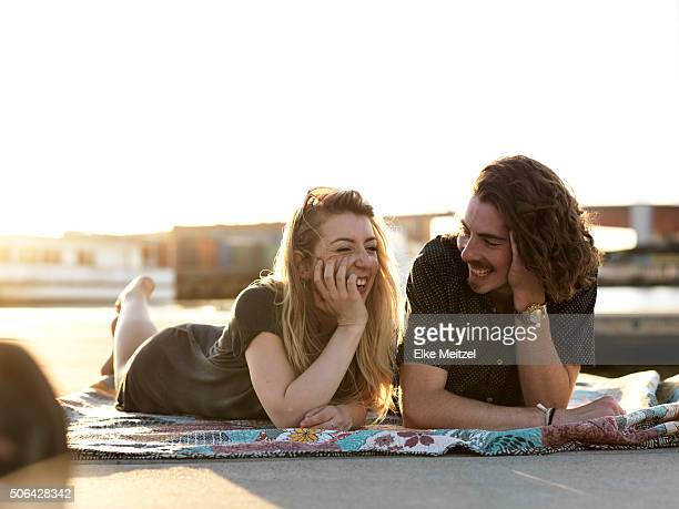 couple lying on blanket laughing together