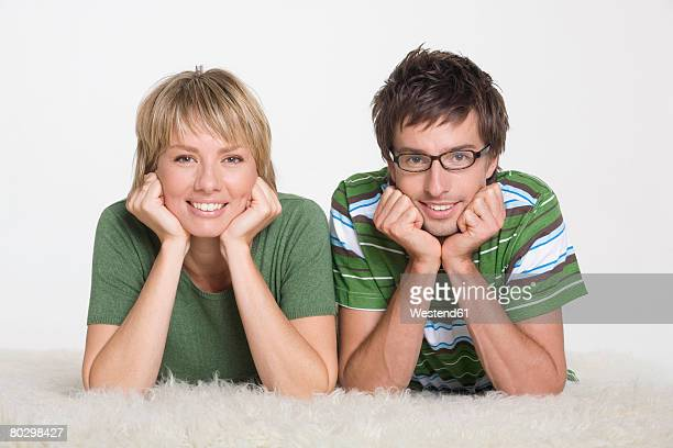 Young couple lying on furry carpet, portrait, close-up