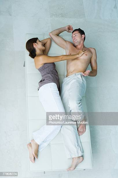 Couple lying on chaise longue together, woman pushing man away, full length, view from above