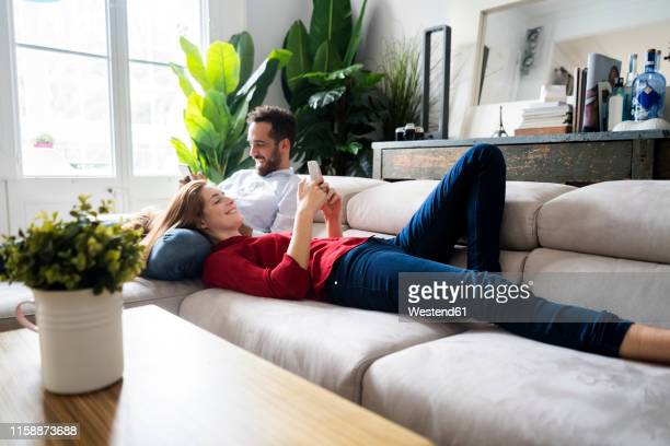 couple lying on couch, using heir smartphones - edificio residencial fotografías e imágenes de stock