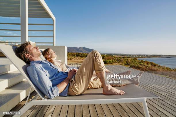 couple lying on deck chairs at luxury beach house - transat photos et images de collection