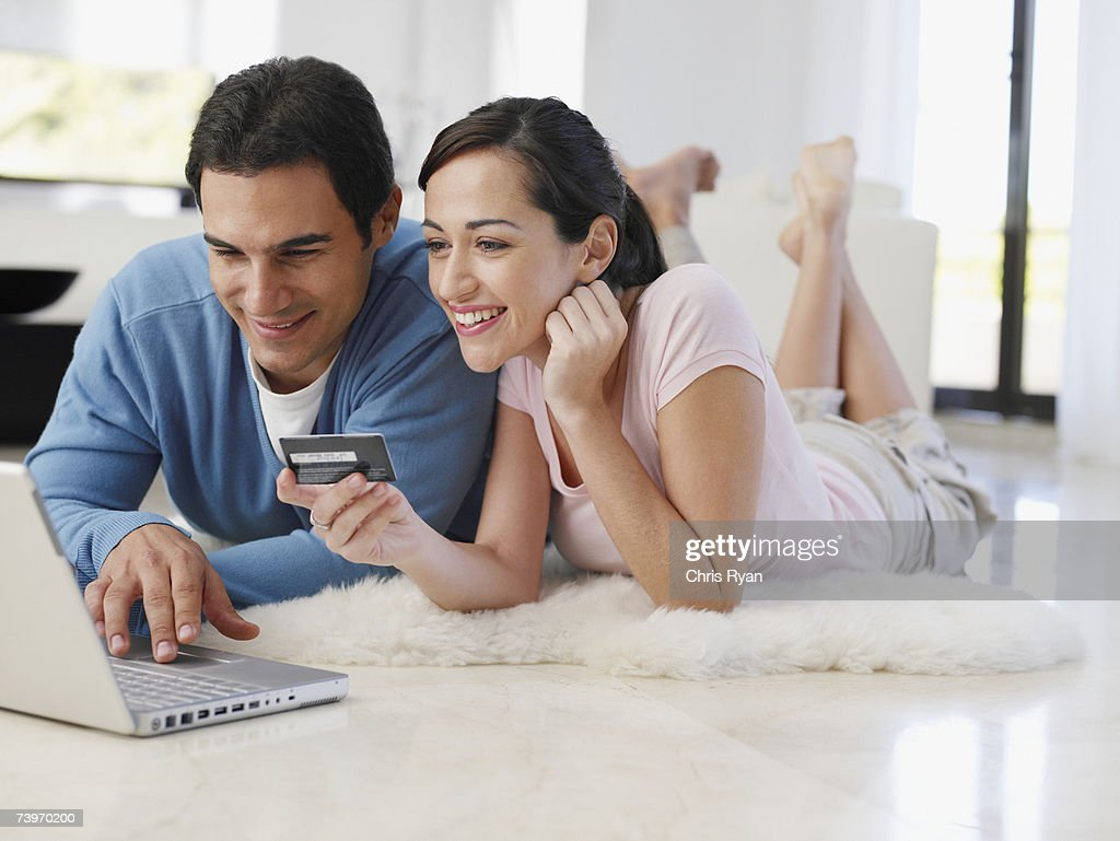 Couple lying on floor at home shopping online with credit card : Stock Photo