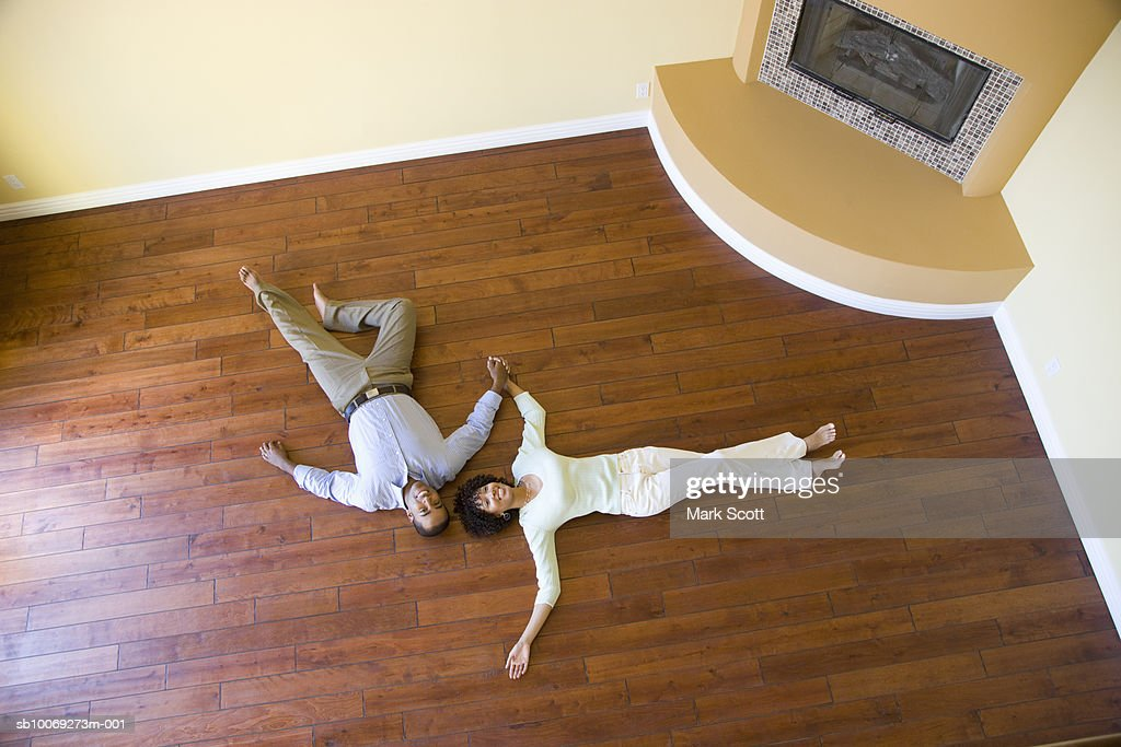 Couple lying on floor at new home, elevated view : Stockfoto