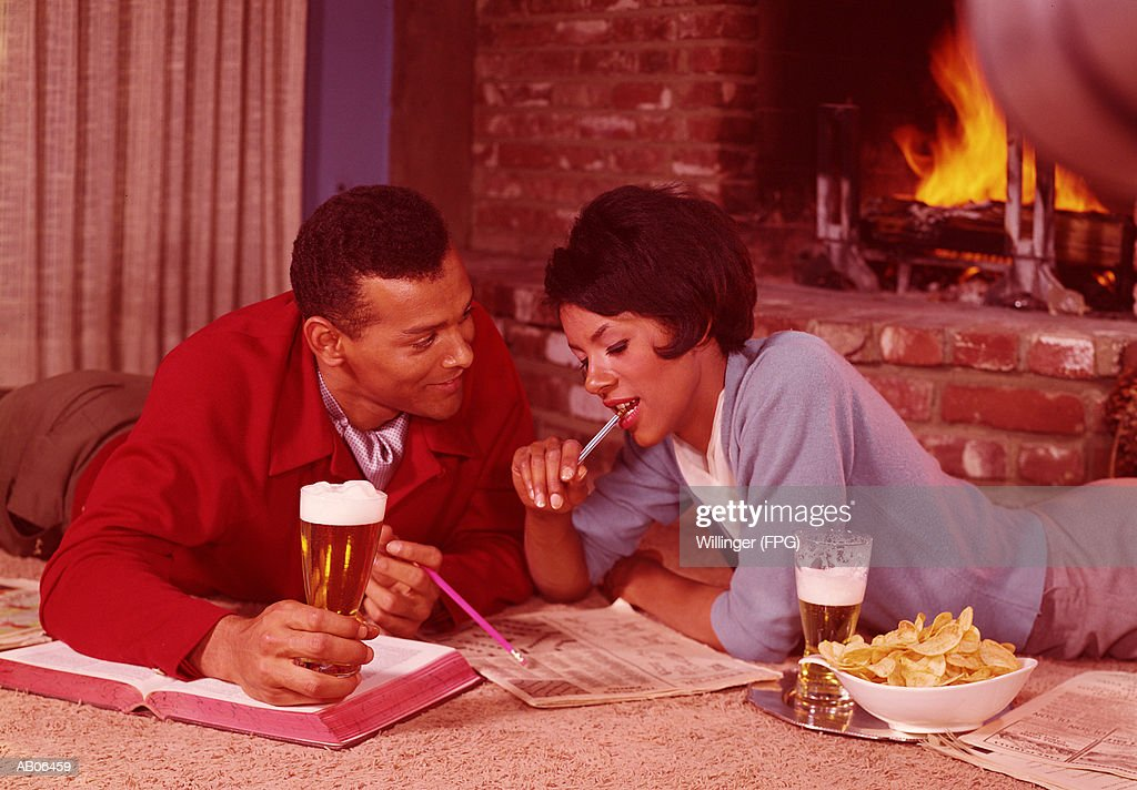 Couple lying on floor by fire, drinking beer and working on crossword : Stock Photo