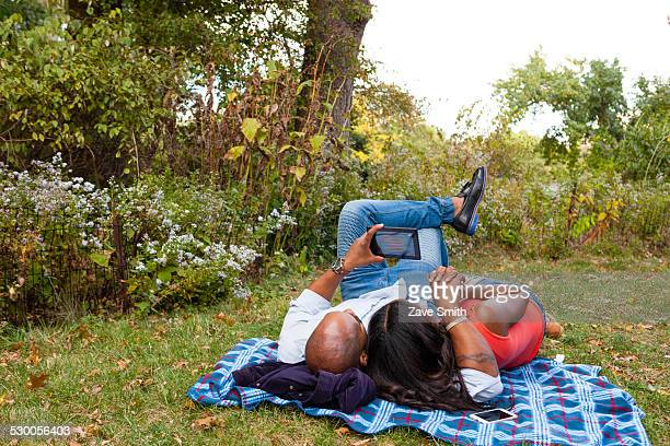 couple lying on grass watching movie on tablet - 動画関連 ストックフォトと画像