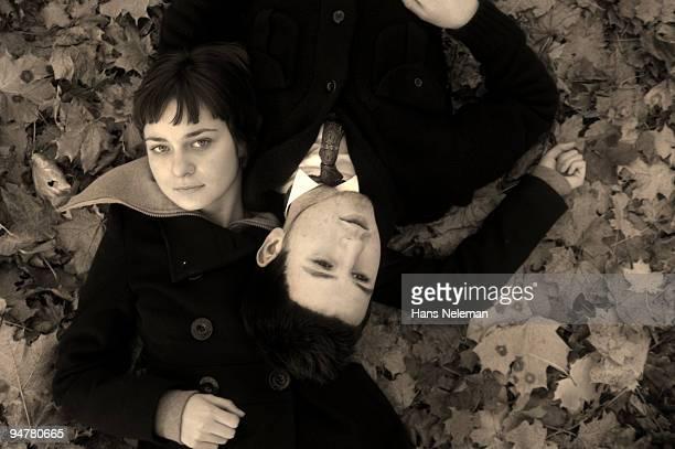 couple lying on leaves in a park, kiev, ukraine - heteroseksueel koppel stockfoto's en -beelden