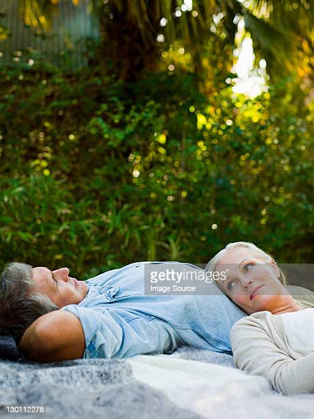 Pärchen auf Picknick-Decke im Garten
