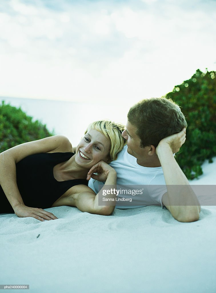 Couple lying on sand side by side : Stockfoto