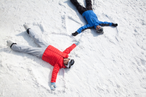 Couple Lying On Snow Making Snow Angel - gettyimageskorea