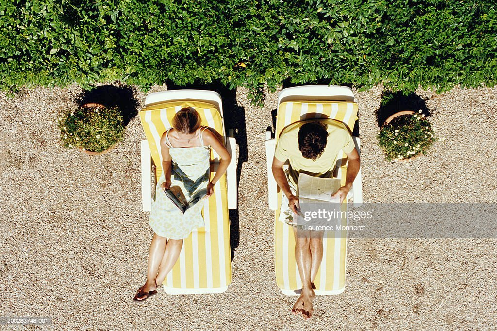 Couple lying on sunbeds reading, overhead view : Stock Photo