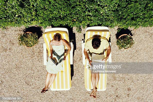 couple lying on sunbeds reading, overhead view - cadeira recostável - fotografias e filmes do acervo