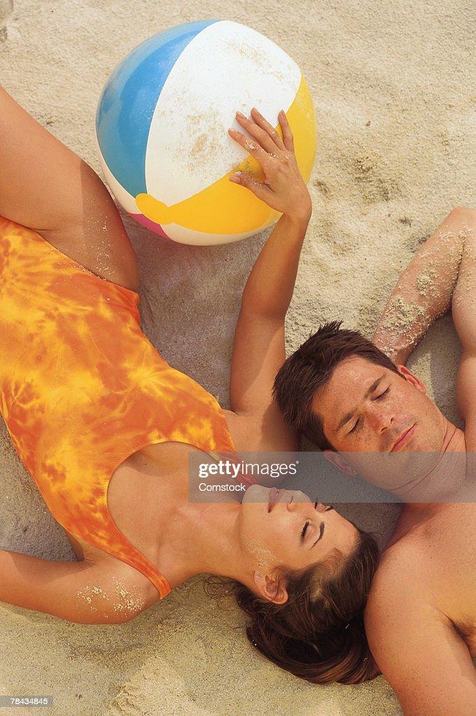 Couple lying on the beach with beach ball : Stock Photo