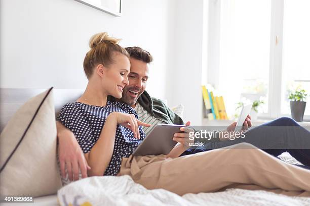 Couple lying on the bed, using a digital tablet together