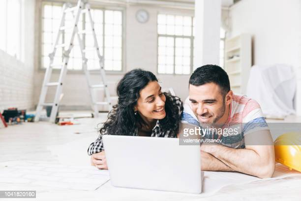 couple lying on the floor in a new apartment and using a laptop - reform stock pictures, royalty-free photos & images
