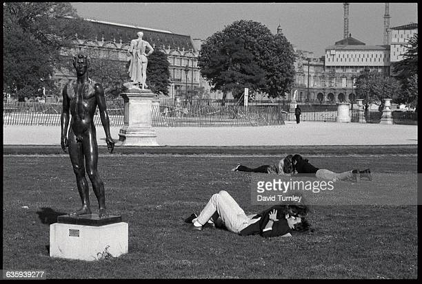 Couple Lying on the Grass near Nude Statue