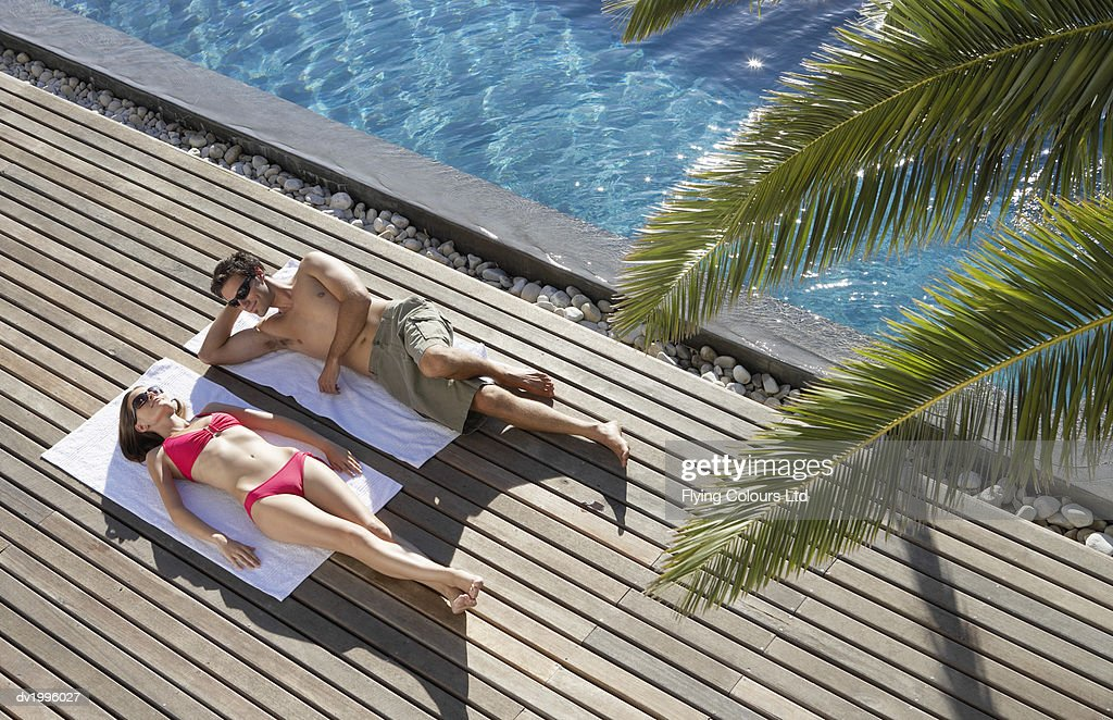 Couple Lying on Towels on Decking, Poolside : Stock Photo