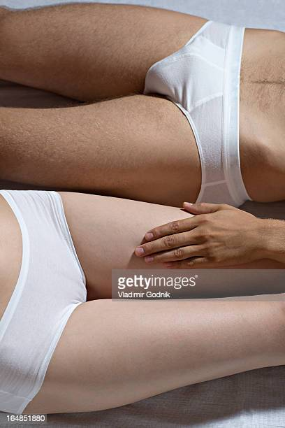 A couple lying side by side, close-up of hips and thighs