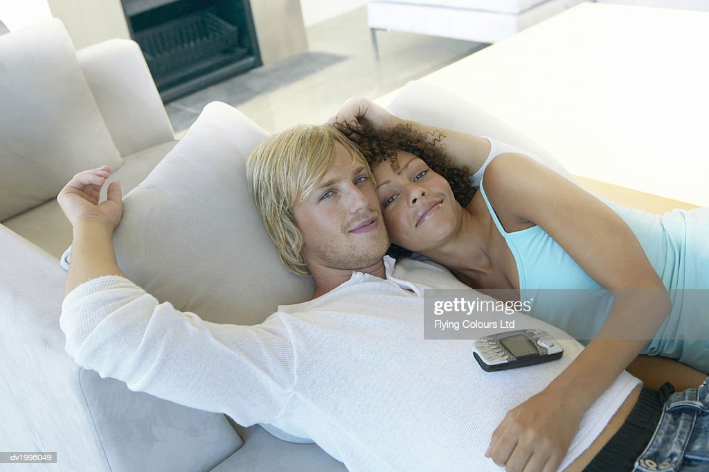 Couple Lying Together on a Sofa in a Living Room : Stock Photo