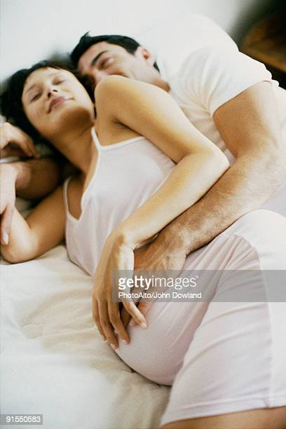 couple lying together on bed, both touching woman's pregnant belly - abbracciarsi a letto foto e immagini stock