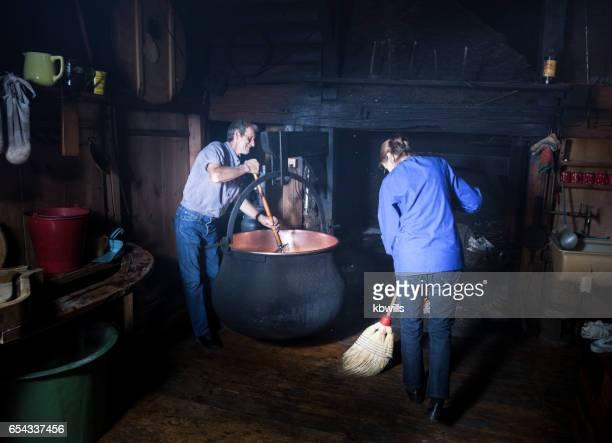 カップルは、スモーキーのスイス マウンテン シャレーの伝統的な方法でチーズを作る - 大釜 ストックフォトと画像