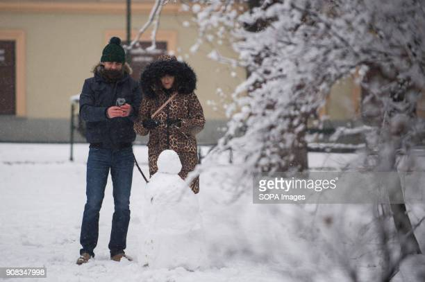 A couple makes a picture of a snowman during winter in Krakow