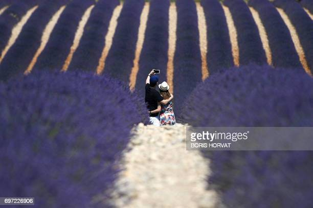 A couple makes a selfie in a lavender field in Valensole southern France on June 18 2017 / AFP PHOTO / BORIS HORVAT