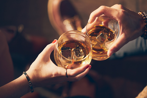 A couple makes a toast with two glasses of whiskey 1092697256