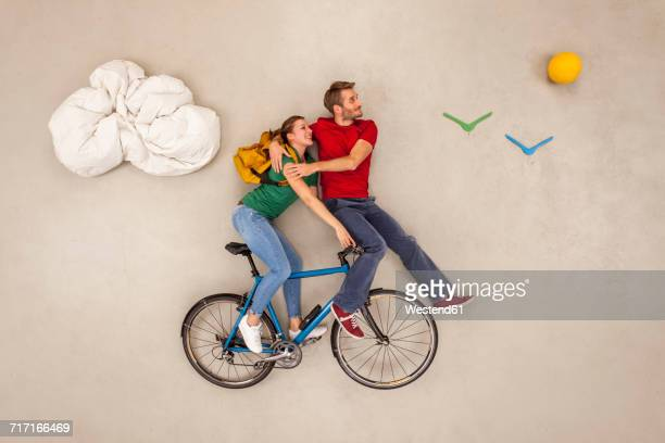 Couple making a bicycle tour on one bike