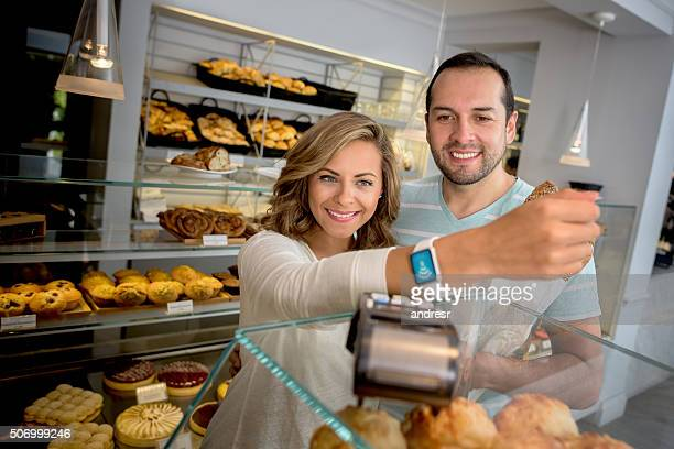 Couple making a contactless payment at the bakery